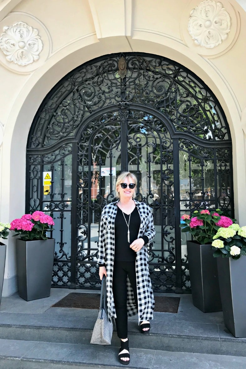Jennifer Connolly of A Well Styled Life wearing a column of black with checked duster