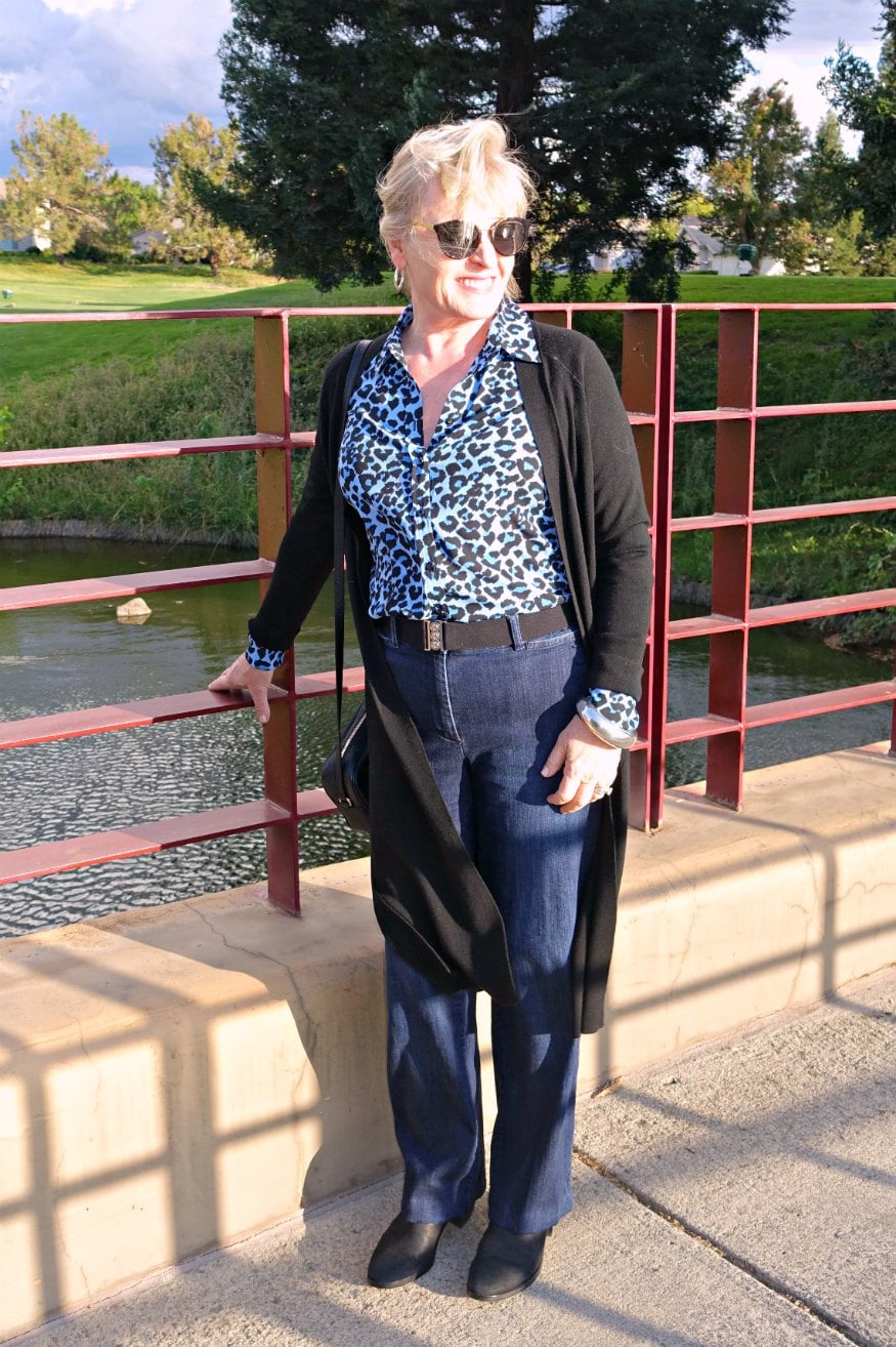 Jennifer Connolly of A Well Styled Life wearing leopard blouse with denim pants and black sweater duster