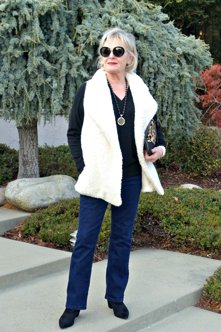 Jennifer Connolly wearing cream fuzzy vest over black v-neck, bootcut jeans and black booties