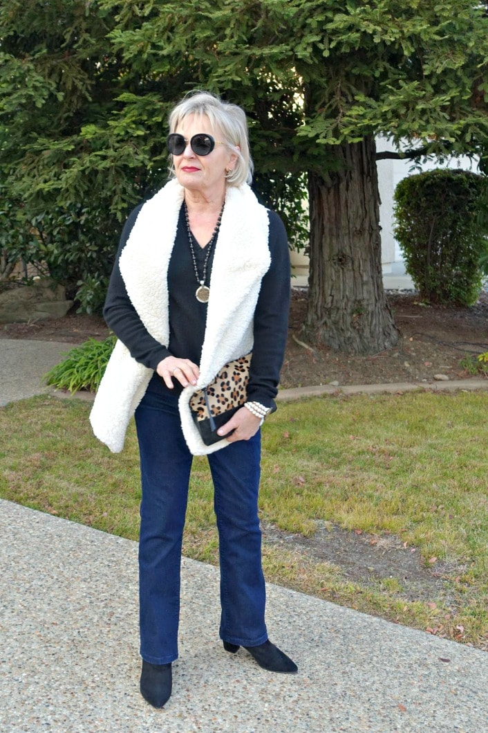 jennifer Connolly of A Well Styled Life wearing fleece vest over v-neck sweater and bootcut jeans