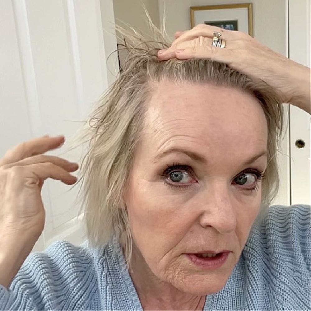 woman examining her thinning hair