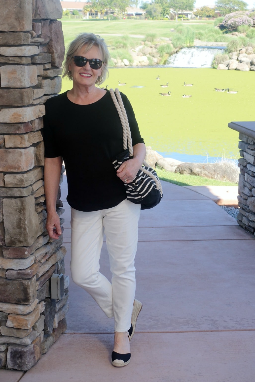 Jennifer Connolly of A Well Styled Life wearing black tee, ivory jeans, black espadrilles and black and ivory striped tote from Walmart