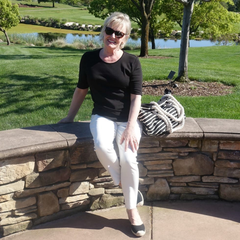 ivory colored jeand and black tee styled with black espadrilles and striped tote on Jennifer of A Well Styled Life