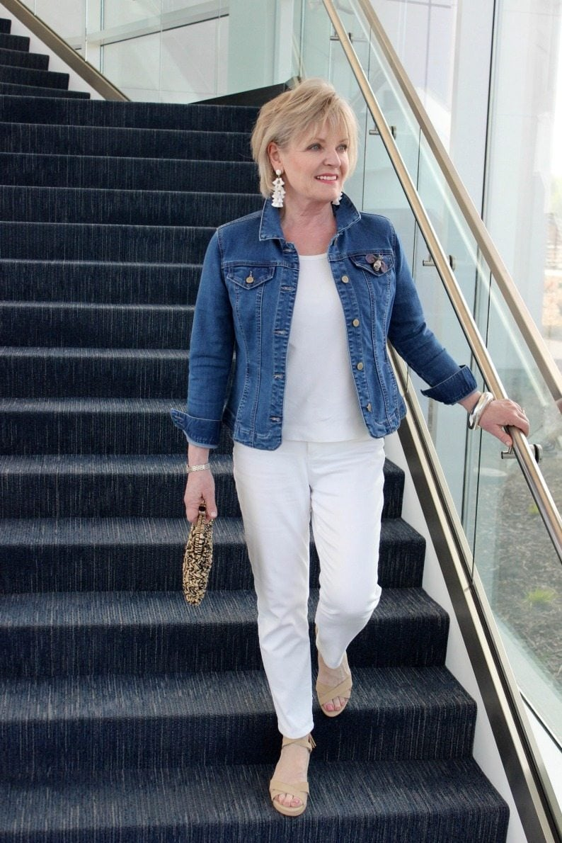 jennifer connolly of a well styled life walking down stairs wearing denim jacket and white jeans