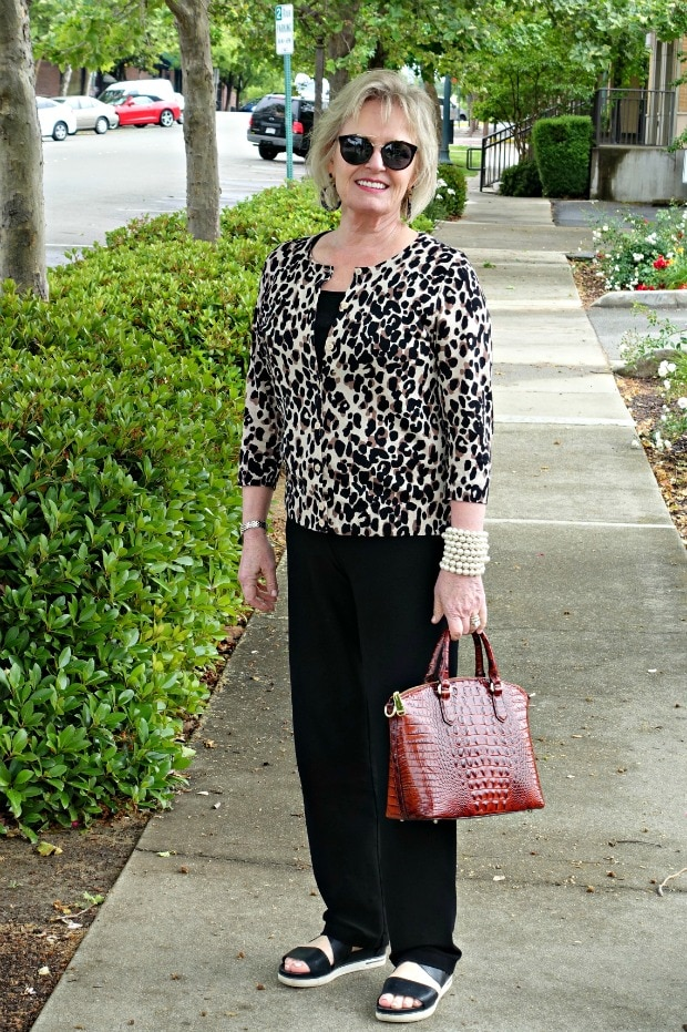 Jennifer Connolly of A Well Styled Life wearing leopard print cardigan, black pants, tortoise print earrings and alligator textured Brahminn handbag