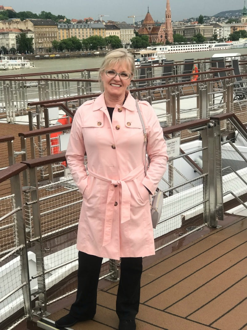 Jennifer Connolly of A Well Styled Life wearing Talbots pink trench coat on a Viking Cruise ship in Budapest pink trench from Talbot with black jeans on a Viking River boat in Bucarest