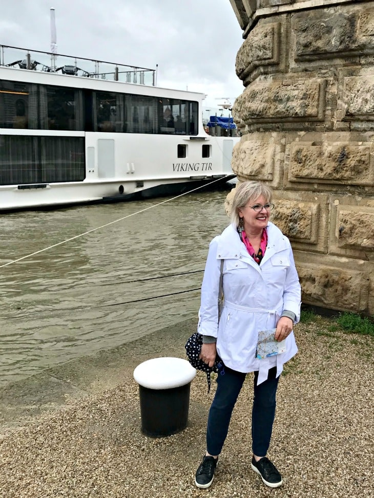 Style blogger Jennifer Connolly of A Well Styled Life next to her Viking River Boat wearing white jacket and Jag jeans
