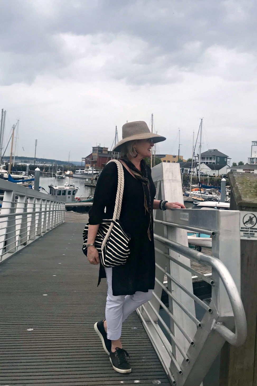 Jennifer Connolly of A Well Styled Life wearing black tunic and white pants with black sneakers and beige hat on the dock at Port Townsend