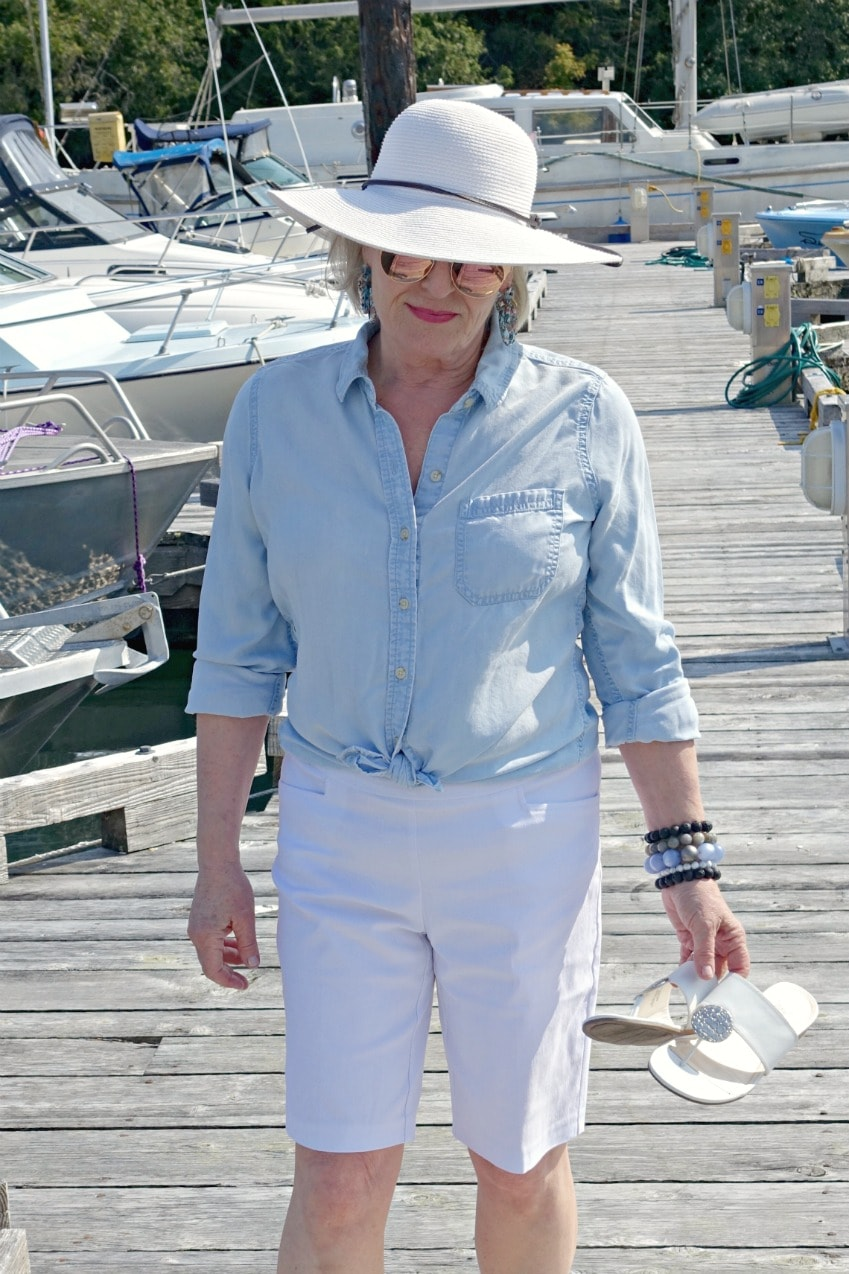 Jennifer Connolly of A Well Styled Life wearing denim shirt, white shorts and white hat on dock in Vancouver Island