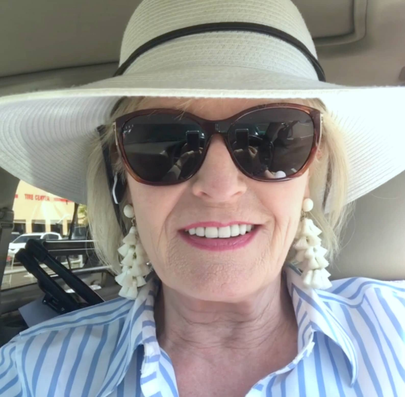 Jennifer Connolly of A Well Styled Life traveling wearing a white hat, white tassel earrings and blue and white striped shirt