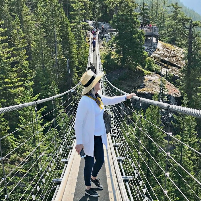 Jennifer Connolly of A Well Styled Life wearing straw hat, white sweater set and deep blue jeans on suspension bridge