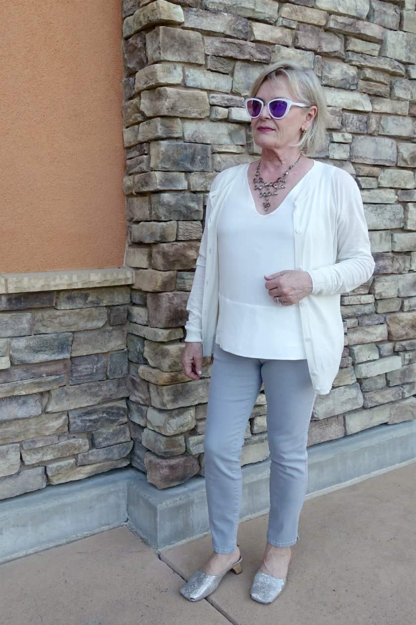 Jennifer Connolly of A Well Styled Life wearing white top and sweater with gray jeans