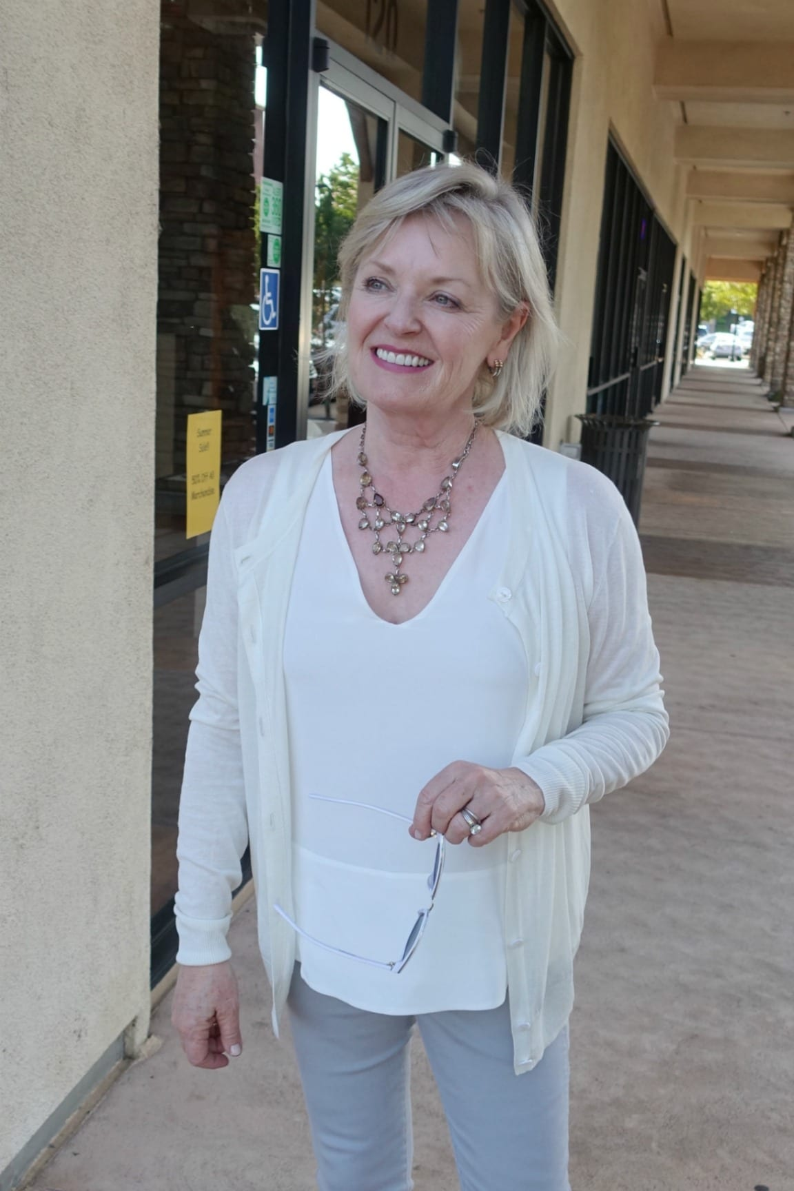 Jennifer Connolly of A Well Styled Life wearing ivory sweater and tank with gray jeans