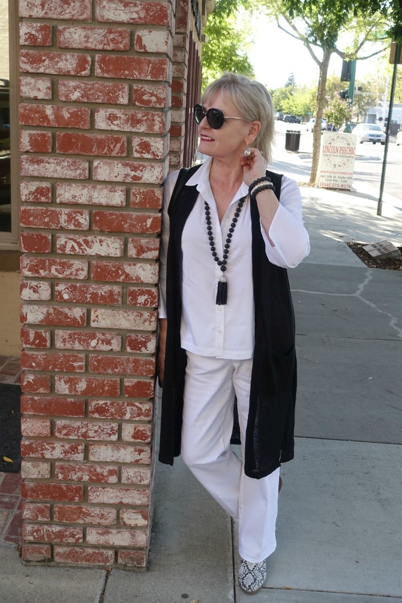 Jennifer Connolly of A Well Styled Life wearing a column of white with black vest from j.jill.