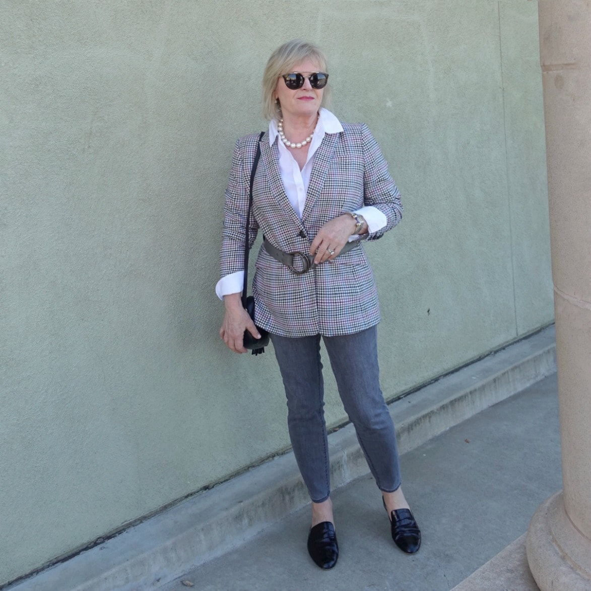 Jennifer Connolly of A Well Styled Life wearing a plaid blazer with belt over skinny gray jeans from Talbots