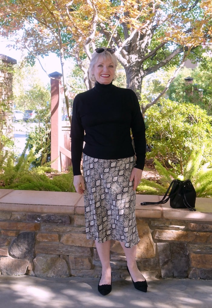 Jennifer Connolly of A Well Styled Life wearing a midi skirt and black turtleneck