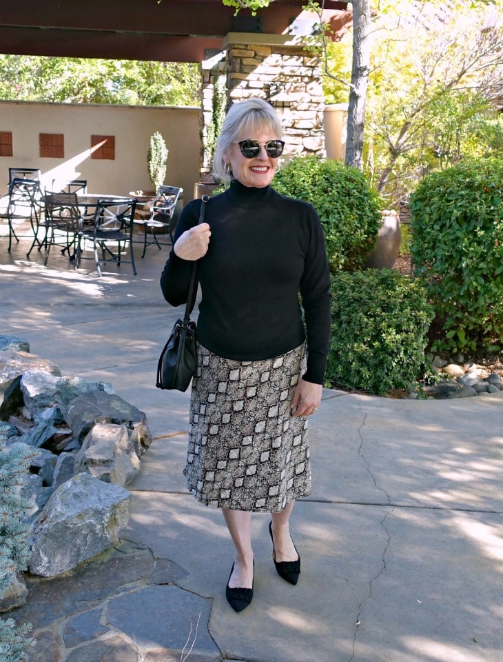 Jennifer Connolly of A Well Styled Life wearing midi skirt with kitten heels and black turtleneck