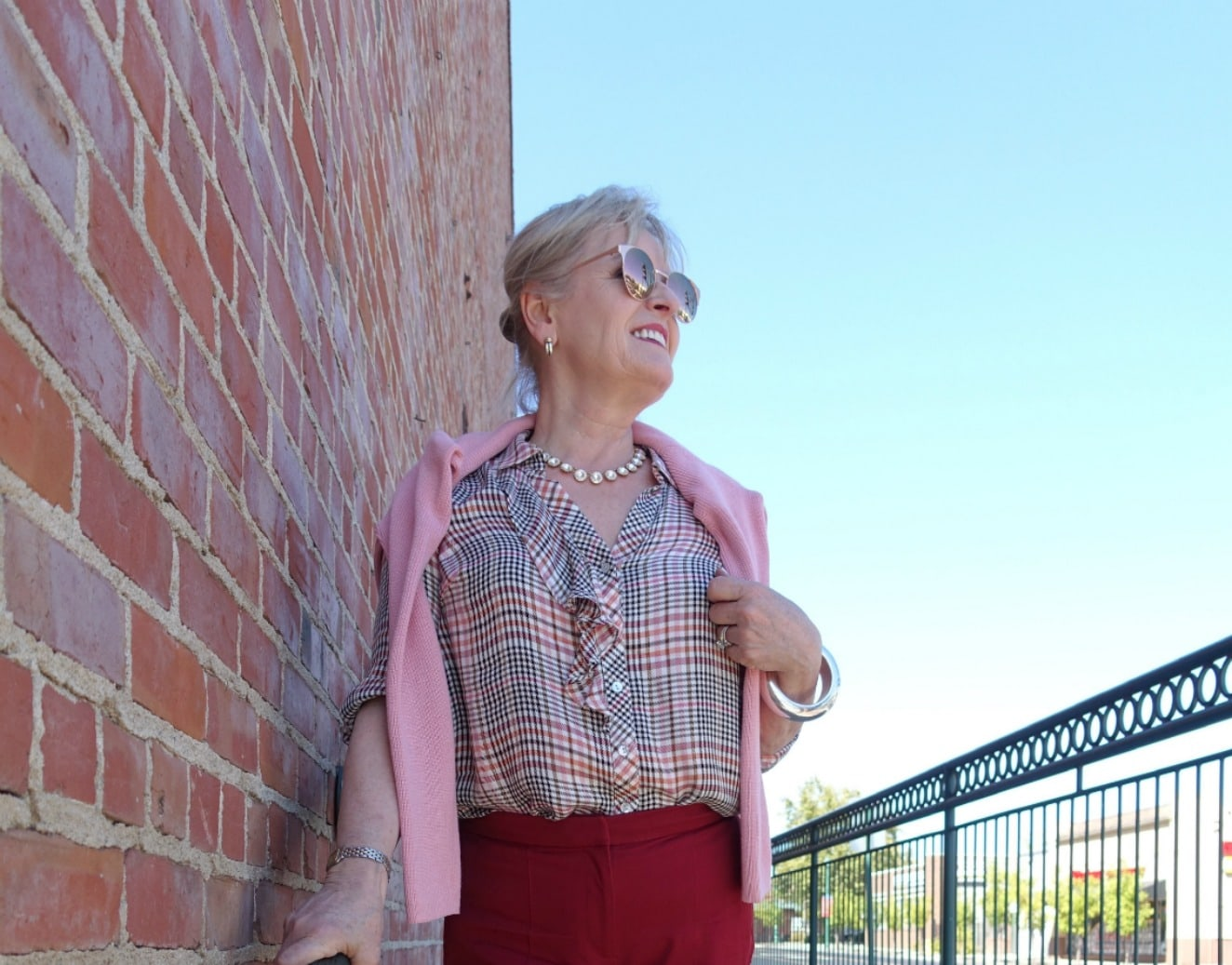 Jennifer Connolly of A Well Styled Life wearing causal plaid shirt with pink sweater over her shoulders
