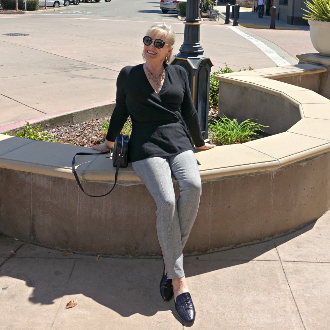 Jennifer Connolly of A Well Styled Life sitting on planter edge wearing the slim Essex pant from Talbots with black sweater
