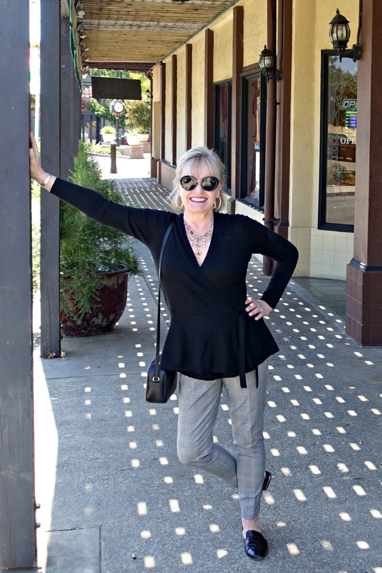 Jennifer Connolly of A Well Styled Life wearing comfortable stretch pants and black sweater on sidewalk
