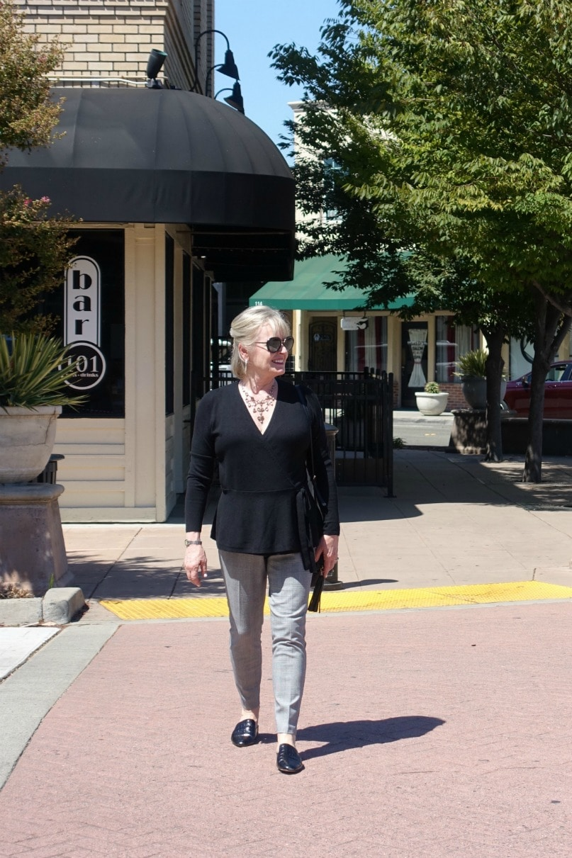 Jennifer Connolly of A Well Styled Life walking across street wearing casual outfit of black sweater and slim plaid pants
