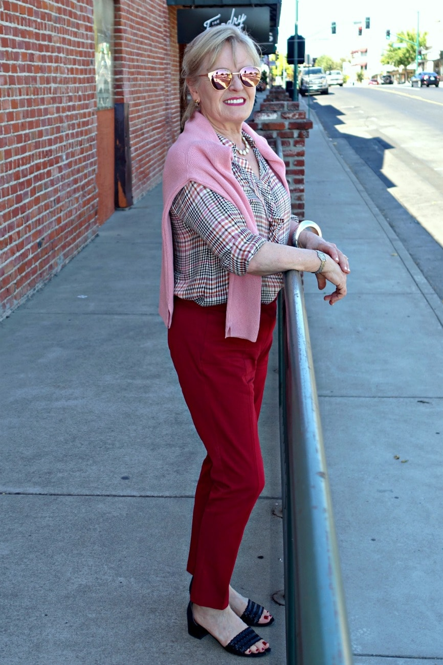 Jennifer Connolly wearing casual outfit with flannel shirt and red pants from J Jill at railing on sidewalk