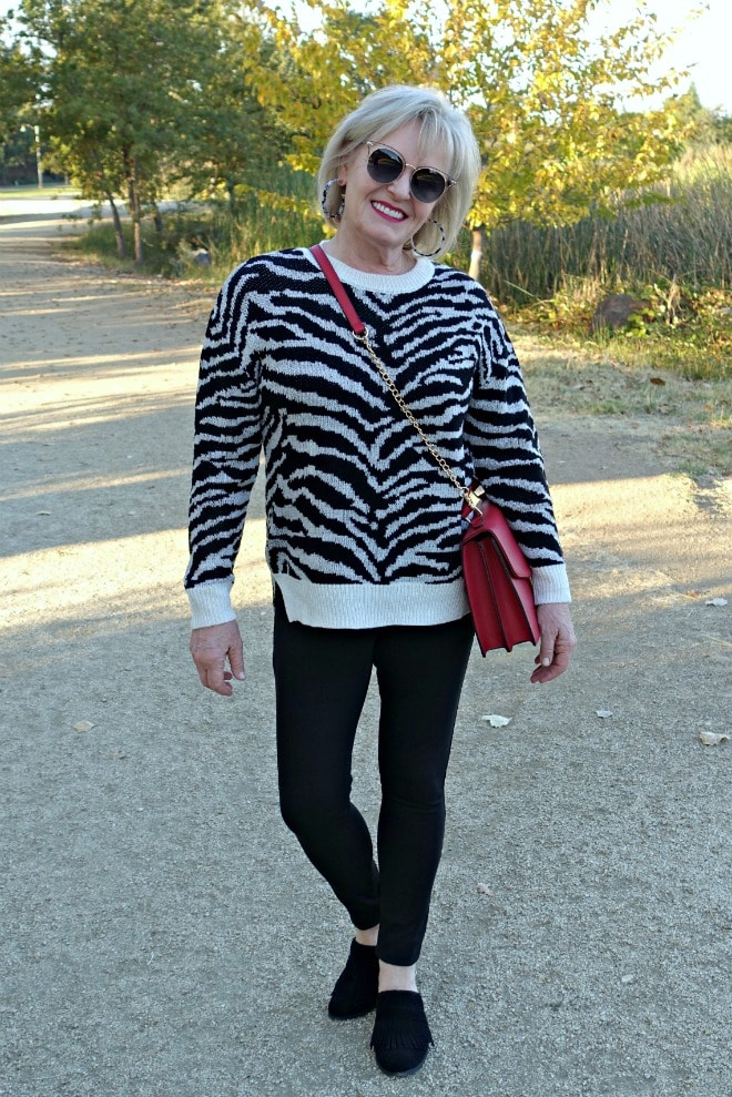 Jennifer Connolly of A Well Styled Life wearing zebra sweater with black jeans and mules