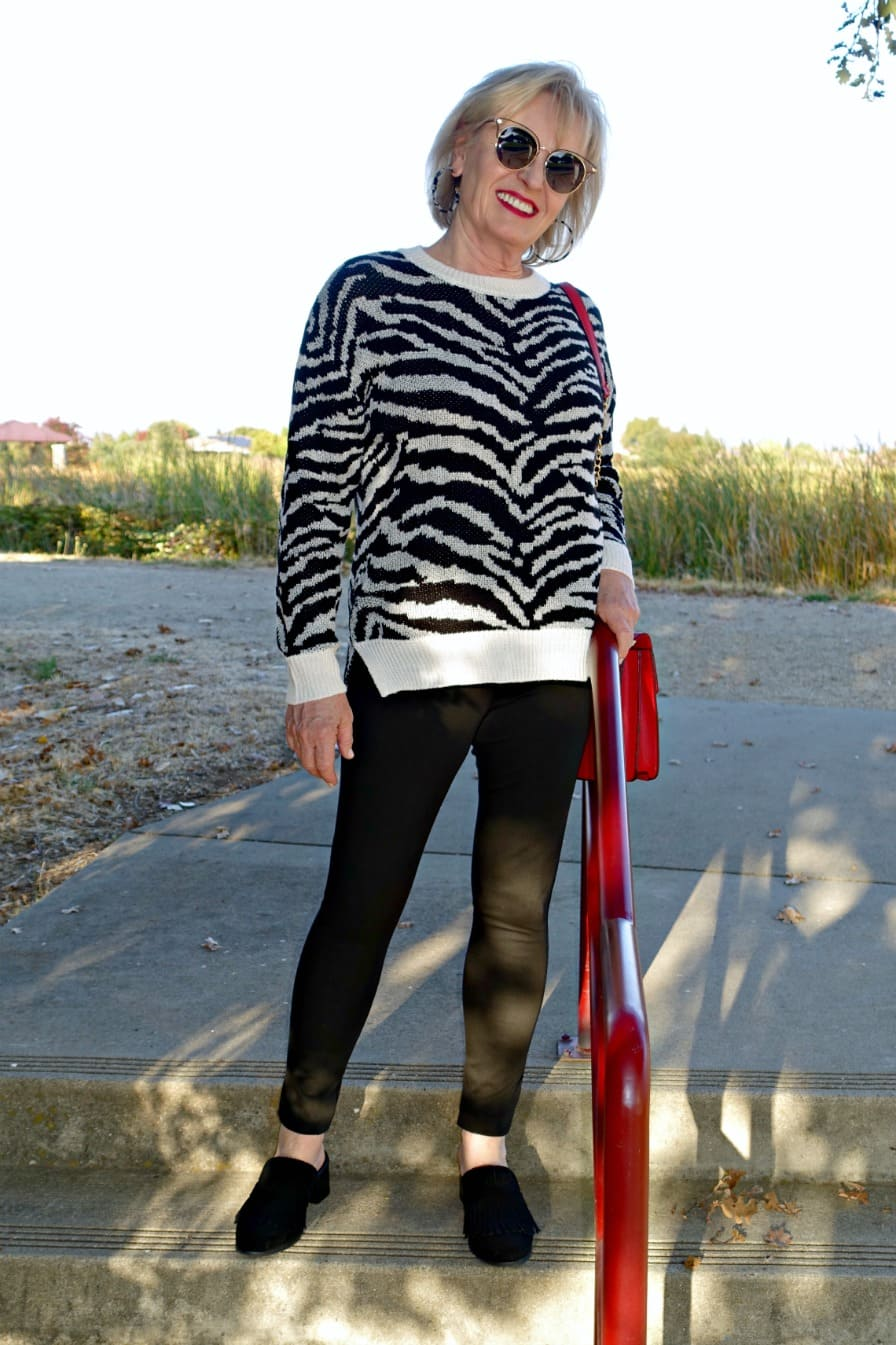 Jennifer Connolly of A Well Styled Life wearing black and white outfit with a tough of red