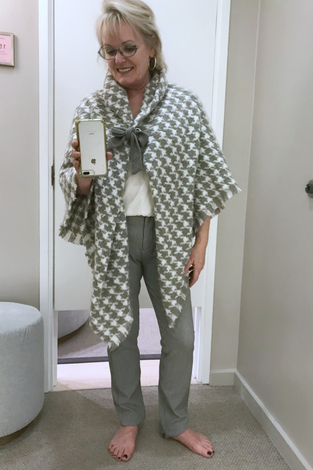 Jennifer Connolly in Ann Tyalor dressing room trying on plaid poncho and tweed leggings