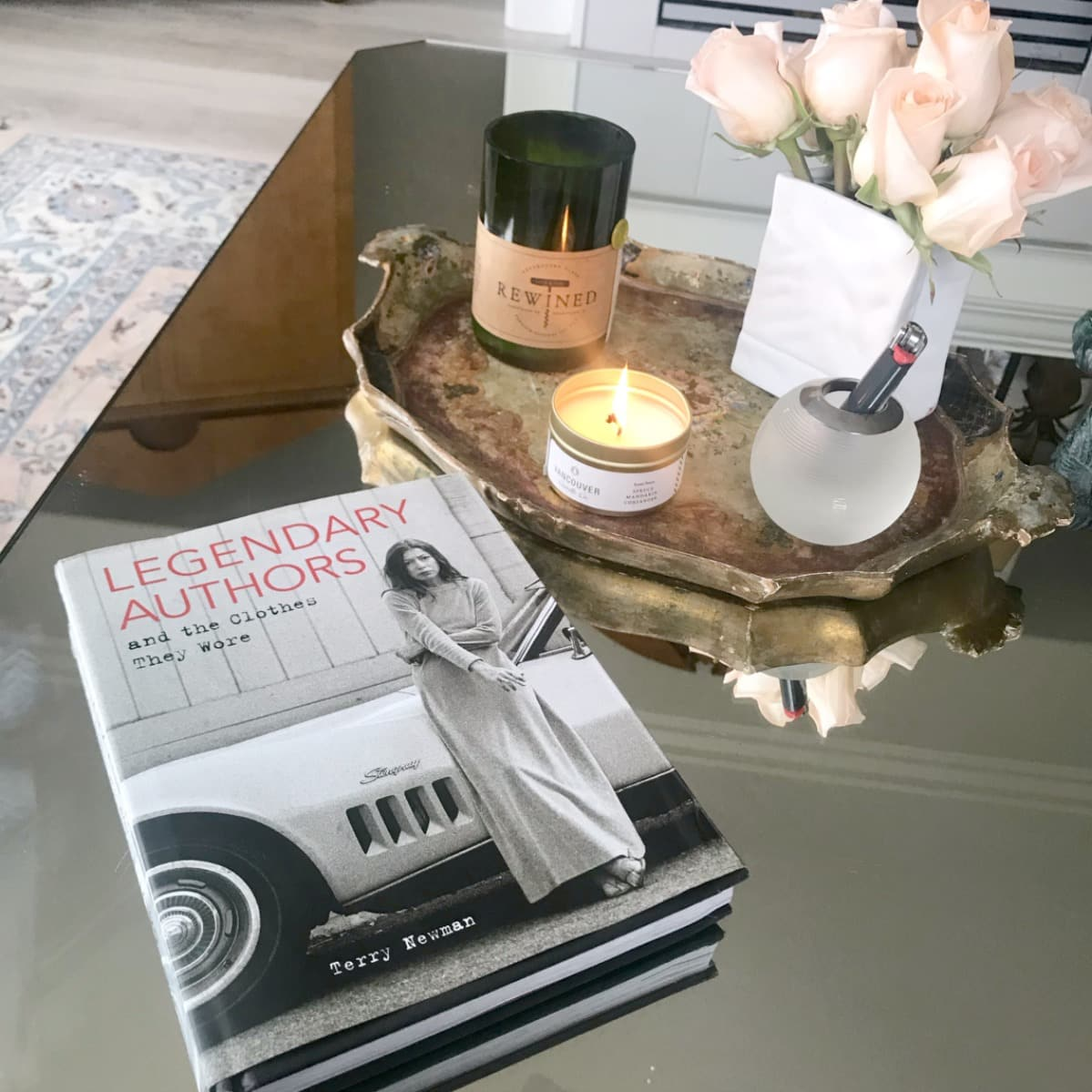 book and several candles on mirrored coffee table