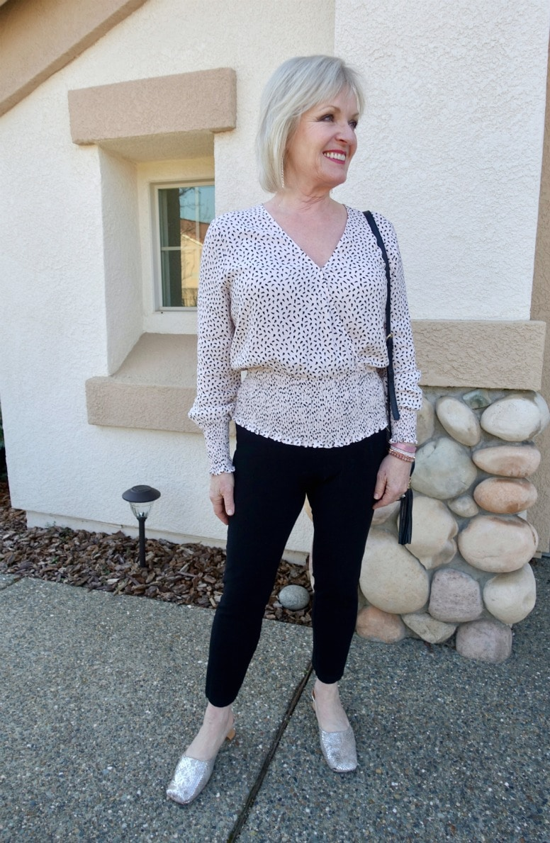over 50 style blogger wearing galentines outfit with pink wrap top and black pants