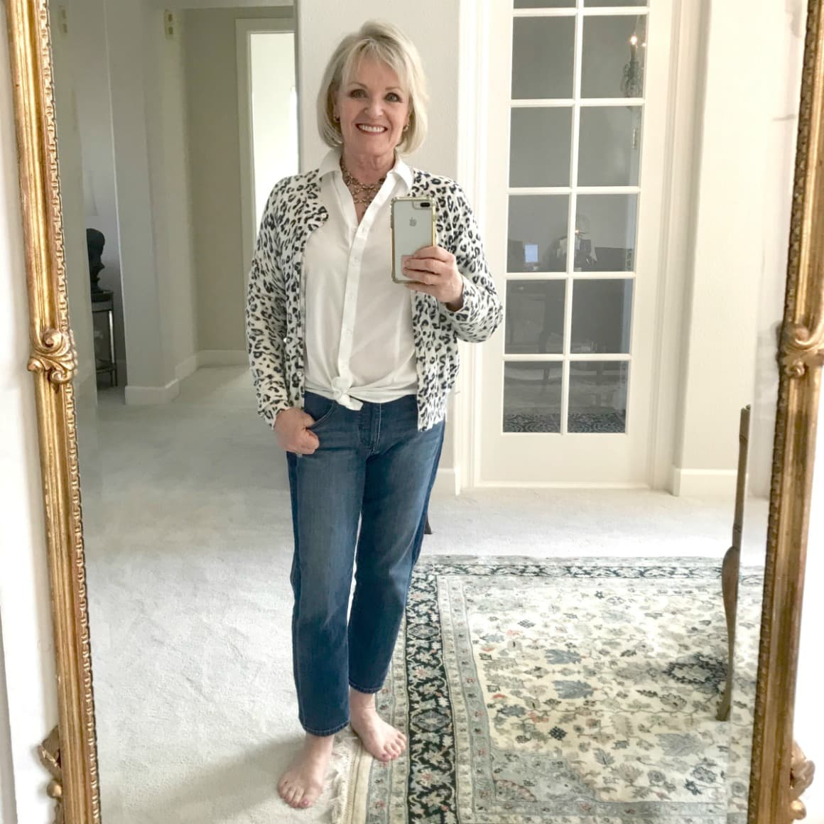 Jennifer Connolly of A Well Styled Life wearing leopard cardigan with white shirt and blue jeans