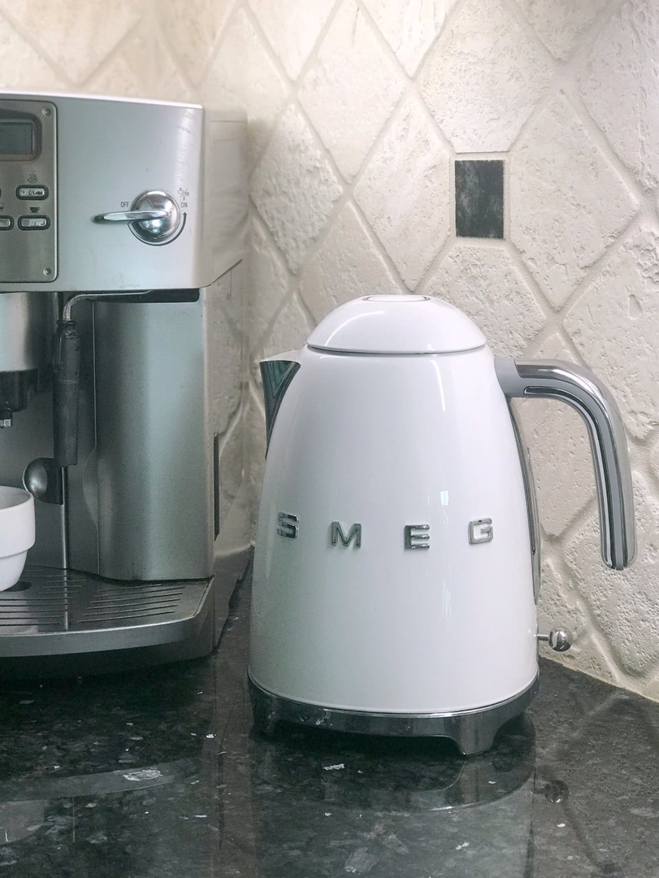 white smeg tea kettle on counter next to espresso machine