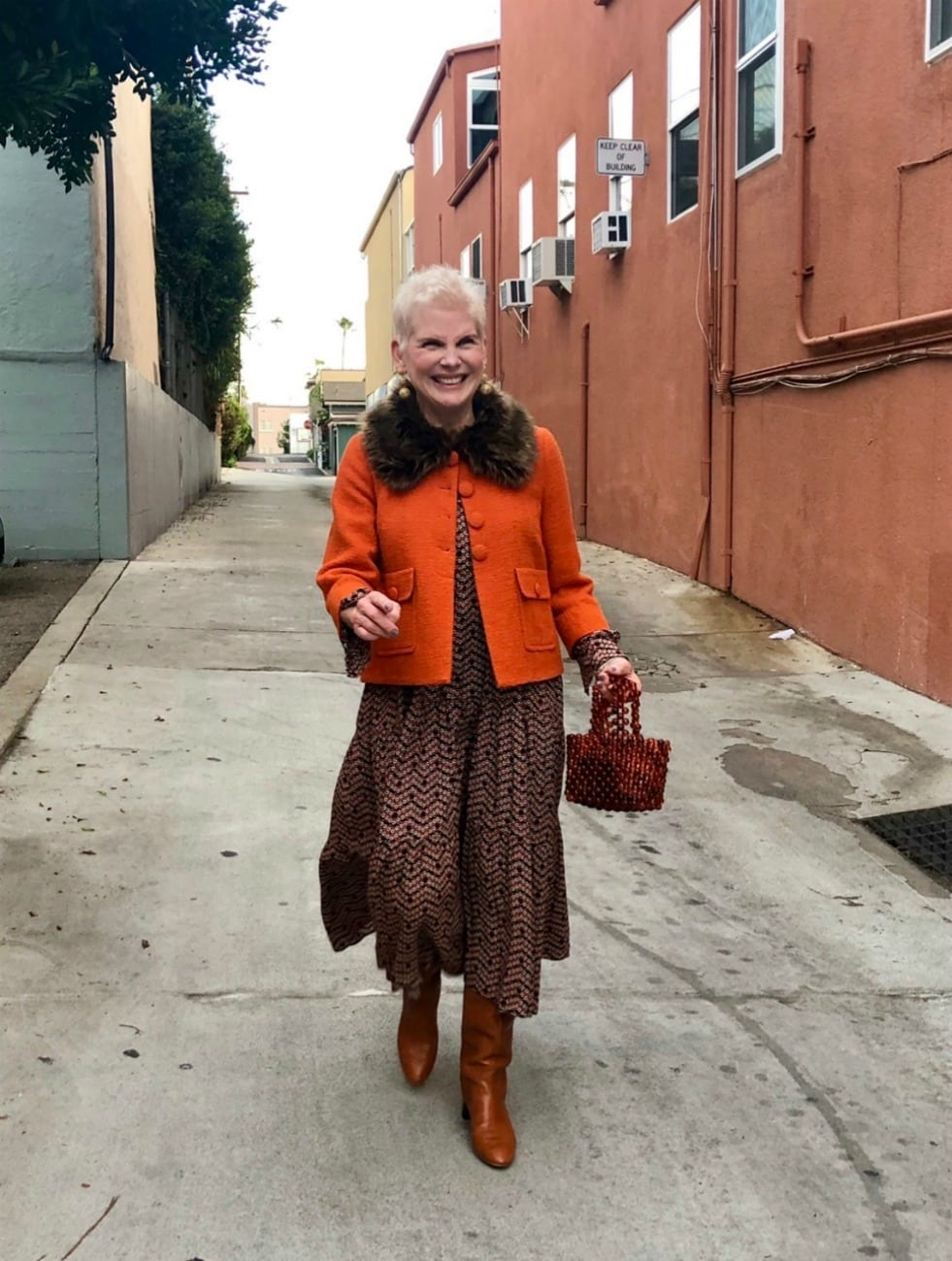woman in brown skirt and orange jacket