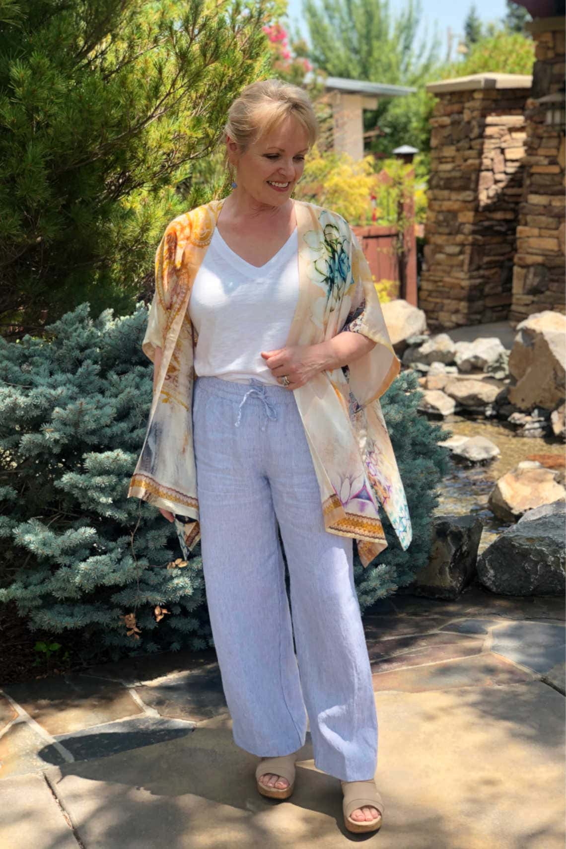 over 50 fashion blogger Jennifer Connolly wearing striped linen pants and silk ruana