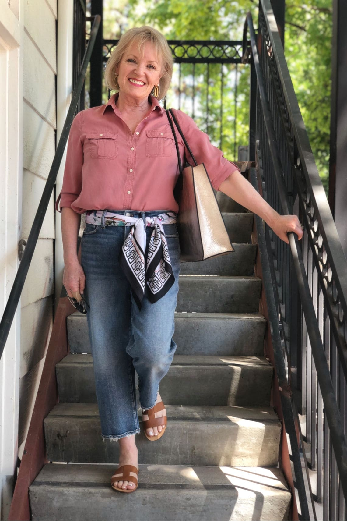 over 50 fashion blogger Jennifer Cobbolly wearing rose colored shirt and blue jeans