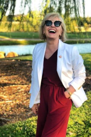over 50 fashion blogger showing how she nails her personal style in white blazer and red jumpsuit