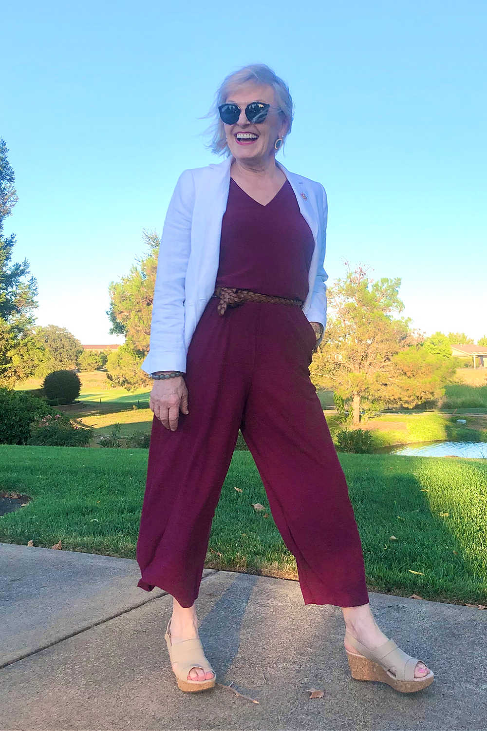 fashion blogger Jennifer Connolly wearing white blazer over burgundy jumpsuit