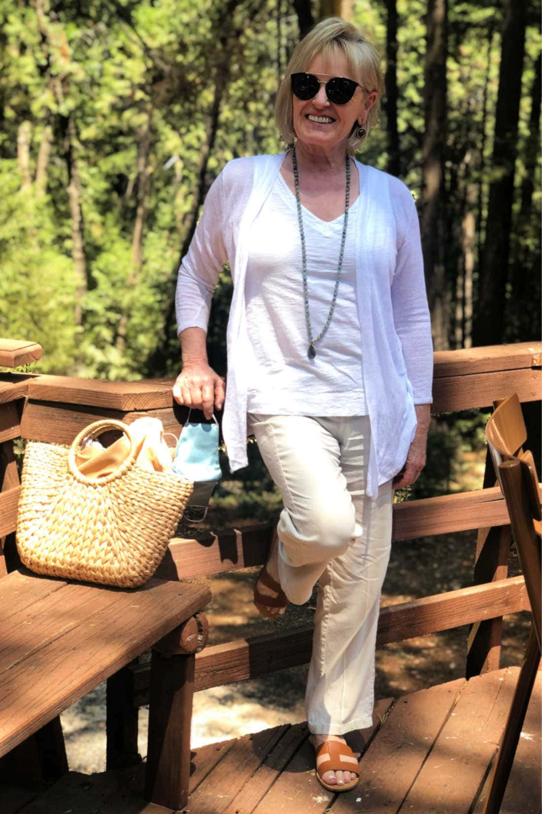 fashion blogger Jennifer Connolly wearing white and beige linin in a forest setting
