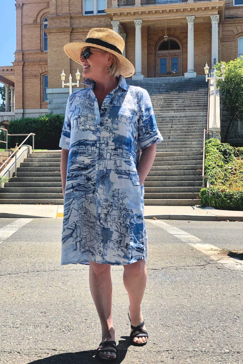 fashion blogger Jennifer Connolly crossing the street wearing blue linen dress from Chicos