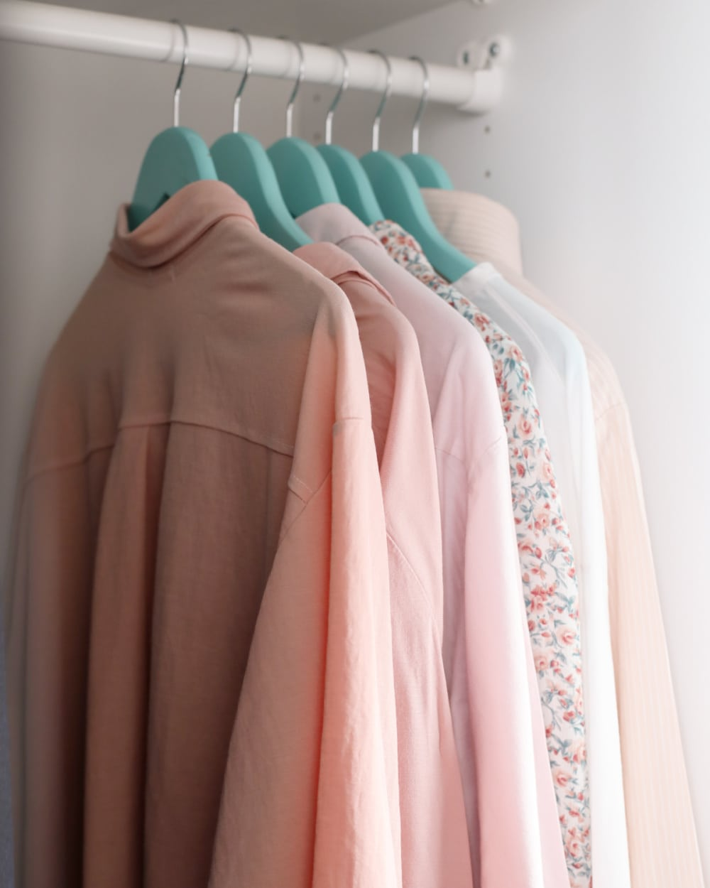 row of pink blouses on closet rod