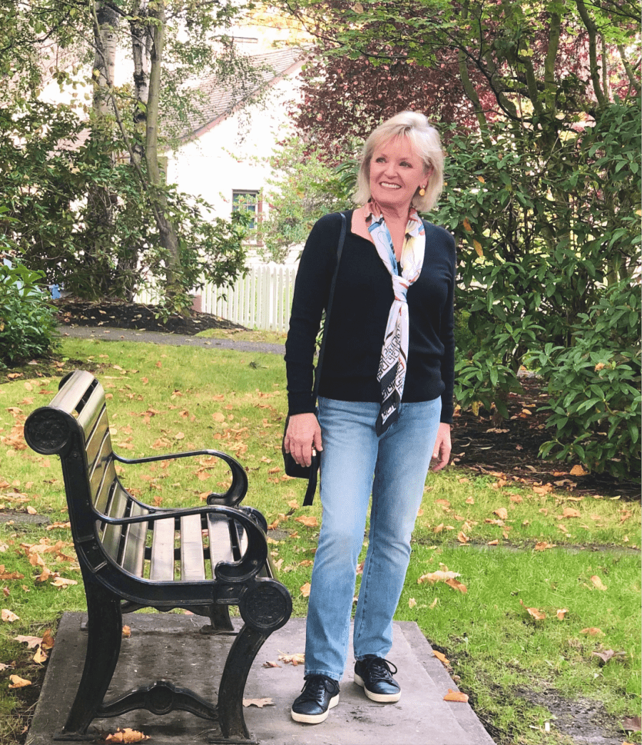 fashion blogger jennifer connolly wearing cashmere sweater and blue jeans in park near bench