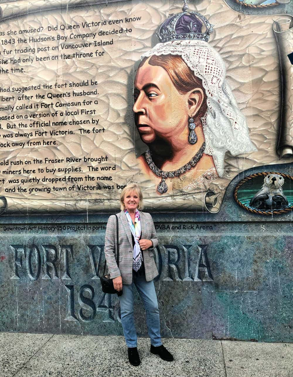 fashion blogger jennifer connolly in victoria bc in front of mural of queen victoria