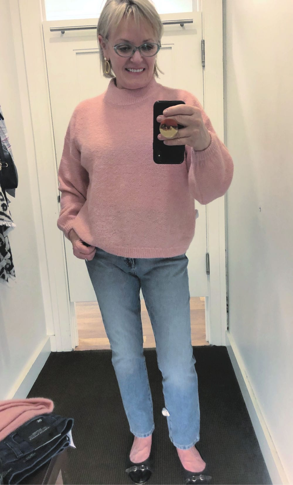 fashion blogger jennifer connolly wearing pink sweater and pale wash blue jeans