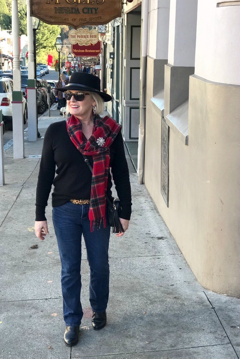 woman wear black hat, plaid scarf and blue jeans