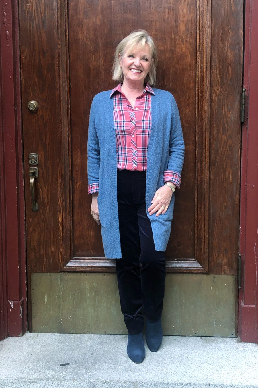 woman leaning against door wearing talbots sweater, shirt and boots