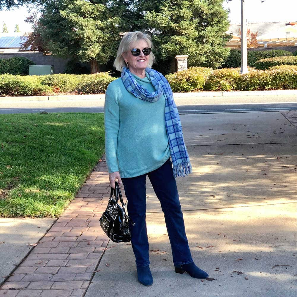 over 50 fashion blogger jennifer connolly of a well styled life wearing blue jeans, plaid scarf and aqua sweater