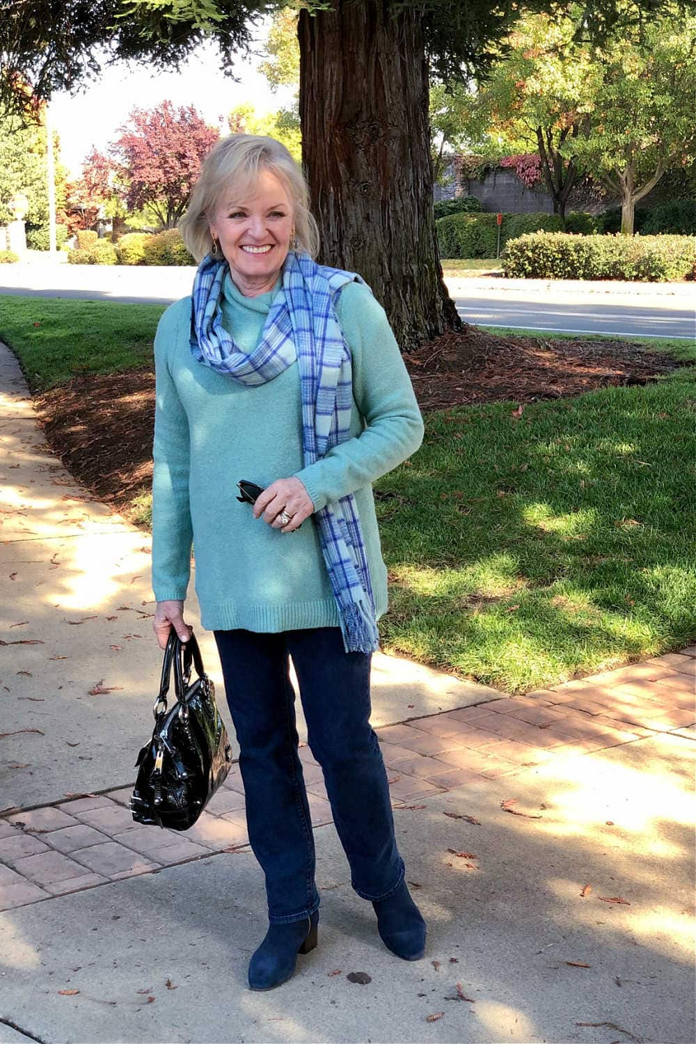 casual outfit with aqaua sweater and blue jeans worn by jennifer of a well styled life