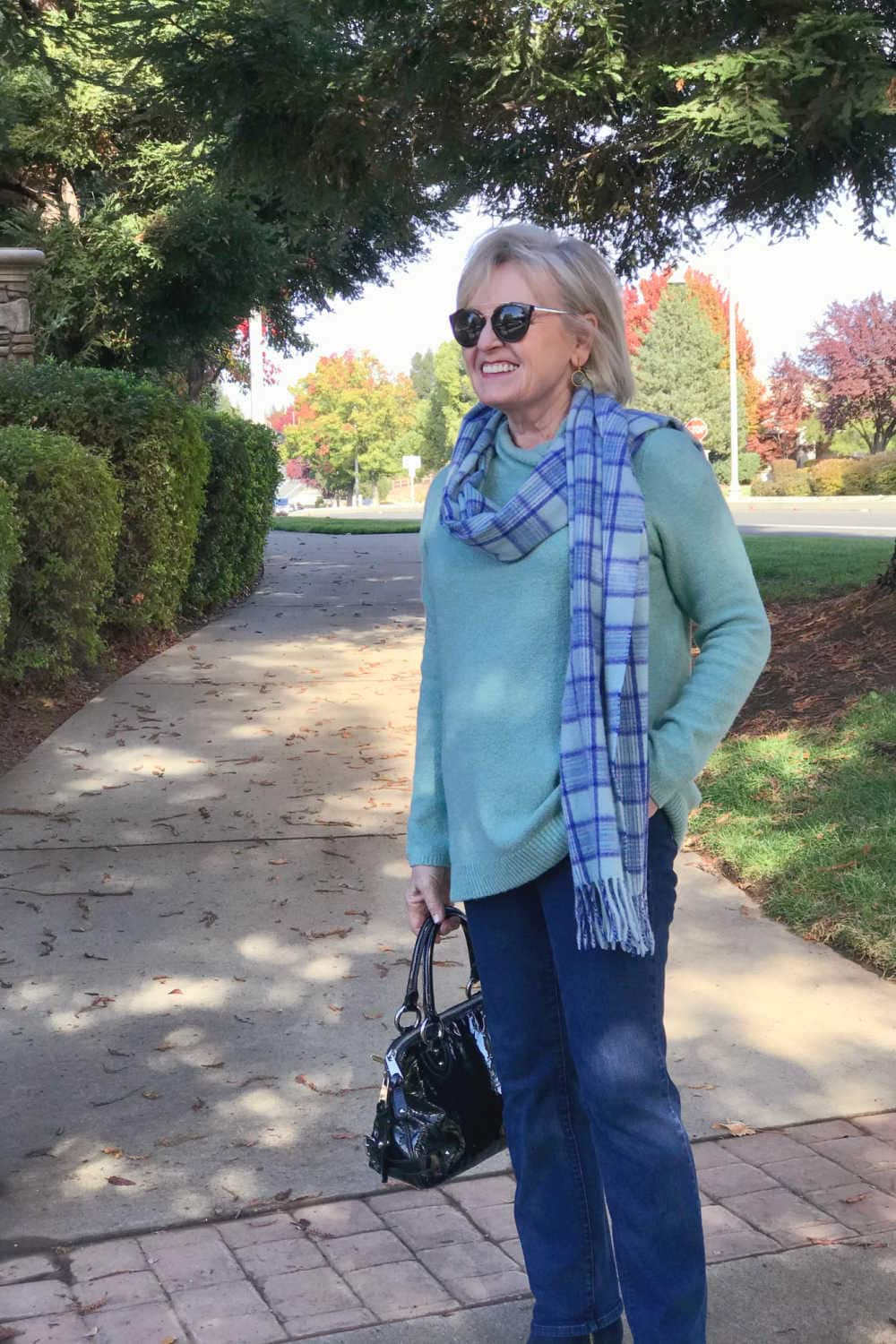 fashion blogger jennifer of a well styled life wearing plaid scarf over aqua sweater with blue jeans