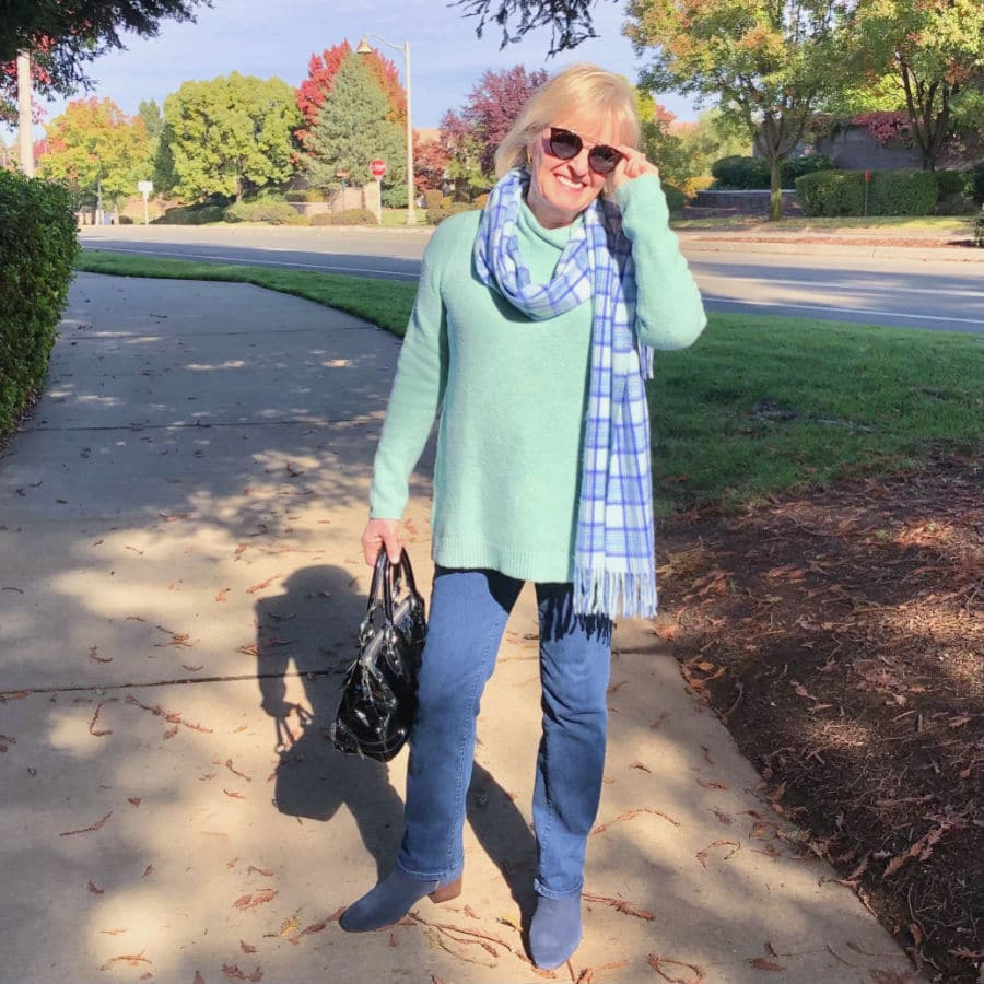 fashion blogger jennifer connolly of a well styled life wearing plaid scarf, boot cut jeans and tunic sweater